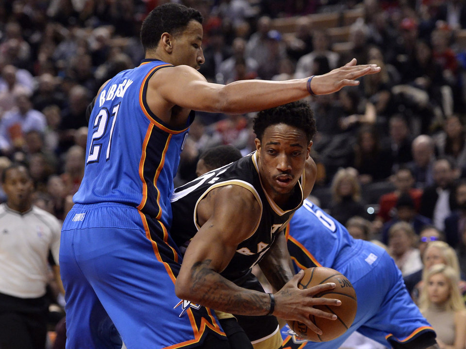 Photo - Toronto Raptors guard DeMar DeRozan (10) looks for a way to the net past Oklahoma City Thunder forward Andre Roberson (21) during the first half of an NBA basketball game Thursday, March 16, 2017, in Toronto. (Nathan Denette/The Canadian Press via AP)