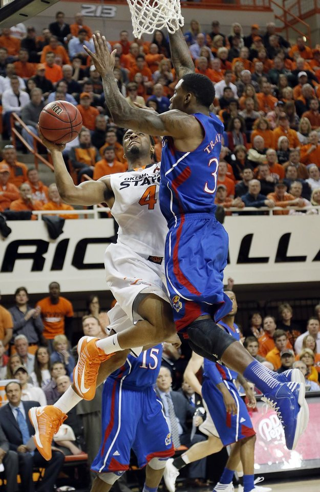 Photo - Oklahoma State 's Brian Williams (4) drives against Kansas' Jamari Traylor (31) during the college basketball game between the Oklahoma State University Cowboys (OSU) and the University of Kanas Jayhawks (KU) at Gallagher-Iba Arena on Wednesday, Feb. 20, 2013, in Stillwater, Okla. Photo by Chris Landsberger, The Oklahoman