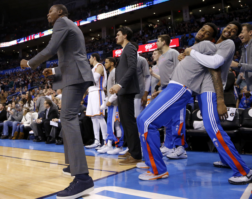 Photo - Oklahoma City's Kevin Durant celebrates in front of Perry Jones and Jeremy Lamb  during an NBA basketball game between the Oklahoma City Thunder and the Philadelphia 76ers at the Chesapeake Energy Arena in Oklahoma City, Wednesday, March 4, 2015. Photo by Bryan Terry, The Oklahoman