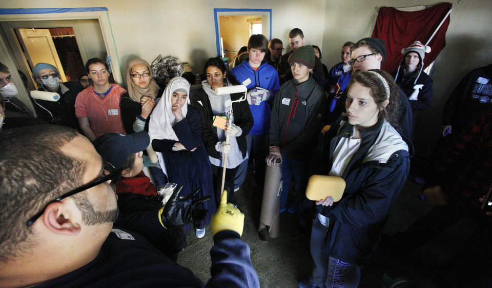 Photo - Volunteers from Mercy and Casady schools listen to painting instructions Monday before they start to fix up a home in Oklahoma City as part of a National Rebuilding Together project in honor of Martin Luther King Jr.  Photos by Paul B. Southerland, The Oklahoman