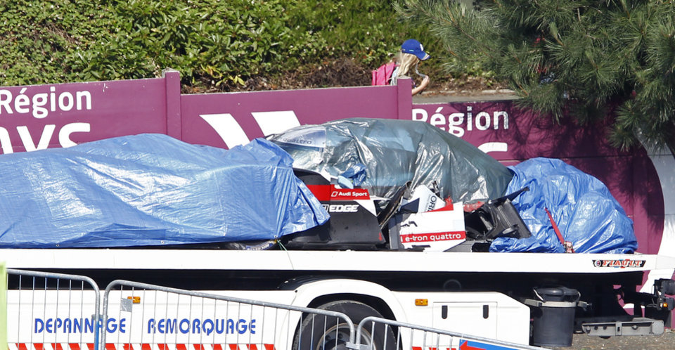 Photo - The remains of the Audi R18 E-Tron No1 driven by Loic Duval of France are brought back to the pits after it crashed during a free practice session for the 24-hour Le Mans endurance race, in Le Mans, western France, Wednesday, June 11, 2014. The race will take place here on Saturday June 14 and Sunday June 15.(AP Photo/Remy de la Mauviniere)
