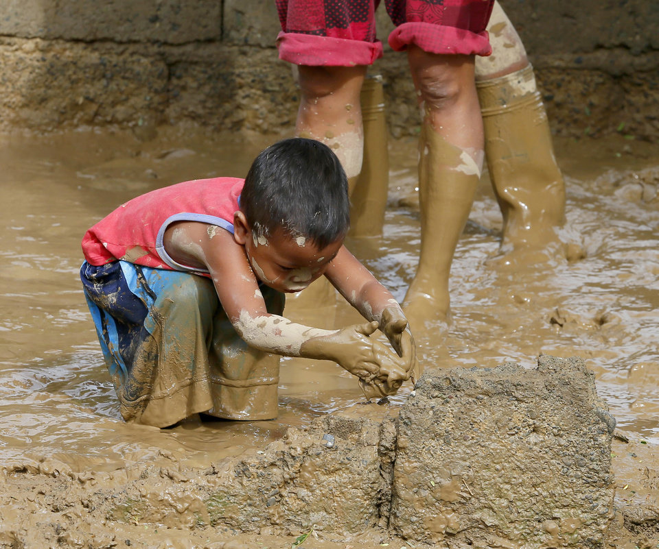 Photo - A boy plays with mud as residents begin cleaning up their homes in Cabanatuan, northern Philippines, Tuesday, Oct. 20, 2015, two days after Typhoon Koppu flooded Cabanatuan city and nearby provinces. Slow-moving Typhoon Koppu blew ashore with fierce wind in the northeastern Philippines early Sunday, toppling trees and knocking out power and communications and forcing the evacuation of thousands of villagers. (AP Photo/Bullit Marquez)
