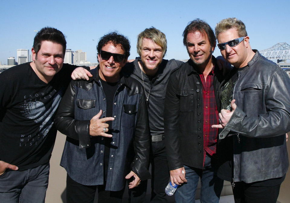 Journey's Jonathon Cain, left, and Neil Schon, second from left, pose with Rascal Flats Joe Dan Rooney, center, Jay DeMarcus and Gary Levox, right, in New Orleans Friday Feb. 1, 2013.  Journey and Rascal Flatts got on stage together for CMT's Crossroads concert Super Bowl weekend.  (AP Photo/ John Carucci)
