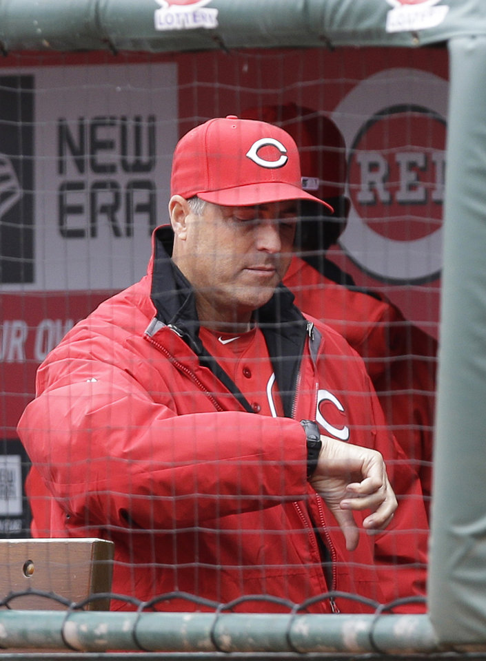 Photo - Cincinnati Reds manager Bryan Price checks the time before a rain-delayed baseball game against the St. Louis Cardinals, Thursday, April 3, 2014, in Cincinnati. (AP Photo/Al Behrman)