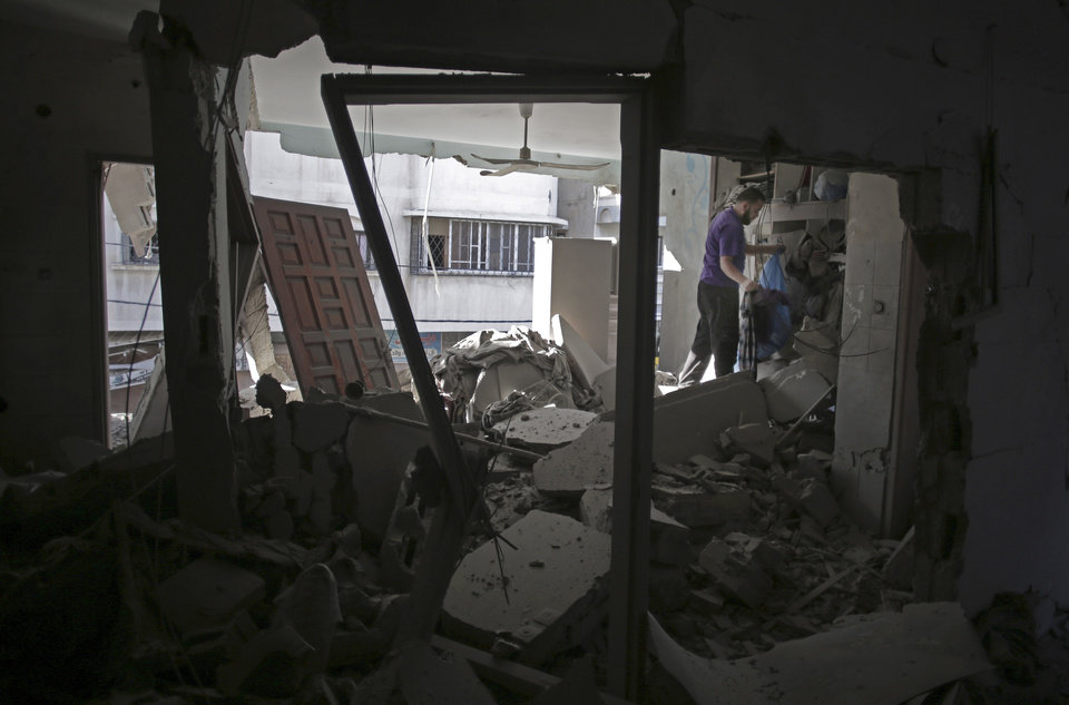 Photo - Palestinians salvage what they can of their belongings from the rubble of their destroyed house following an early morning Israeli missile strike in Gaza City, Wednesday, July 16, 2014. Israel on Wednesday intensified air attacks on Hamas targets in the Gaza Strip following a failed Egyptian cease-fire effort, targeting the homes of four senior leaders of the Islamic militant movement and ordering tens of thousands of residents to evacuate border areas. (AP Photo/Khalil Hamra)