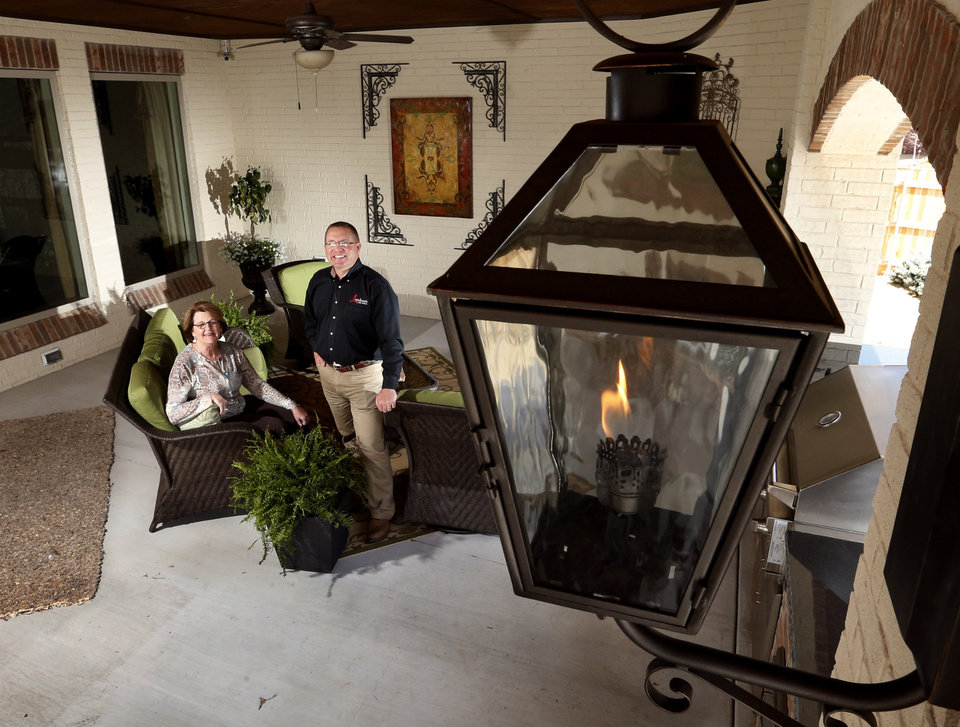 Dan Reeves of Landmark Fine Homes and Pam Hall of Oklahoma Natural Gas stand in the outside living area featuring gas light fixtures and a gas log fireplace at 4500 Northfields, a concept home that uses Compressed Natural Gas, as well as other features on Friday, April 5, 2013 in Norman, Okla.  Photo by Steve Sisney, The Oklahoman