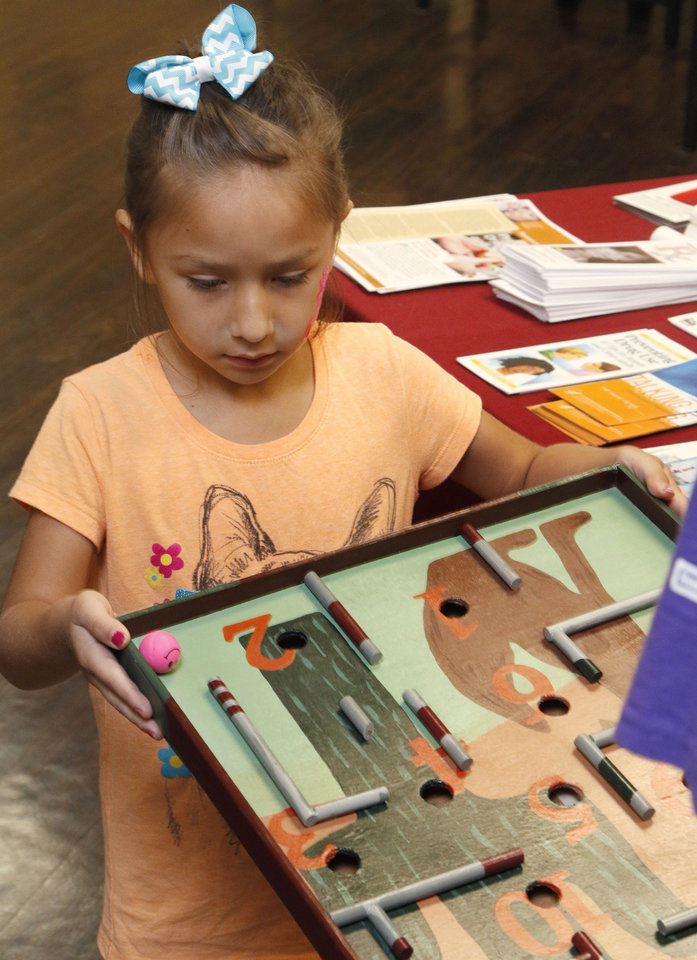 Photo -  Jacey Wade, 4, plays a game during the back-to-school health fair. Photo by Paul Hellstern, The Oklahoman   PAUL HELLSTERN