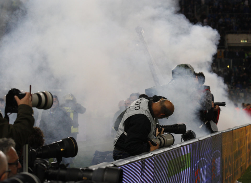 Photo - Photographers are covered by smoke from flares and fireworks thrown by supporters during the Italian Cup final soccer match between Fiorentina and Napoli Rome's Olympic stadium, Saturday, May 3, 2014. (AP Photo/Alessandra Tarantino)