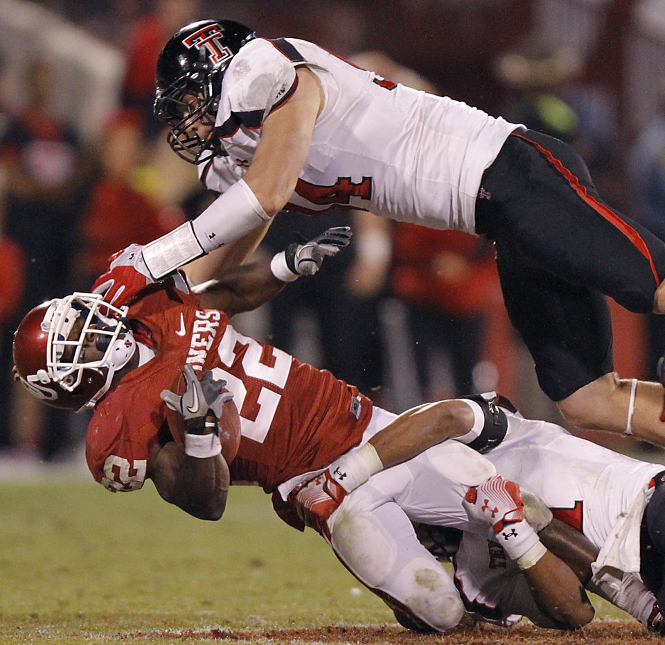 Oklahoma's Roy Finch (22) is brought down by Texas Tech's Scott Smith (94) and Terrance Bullitt (1) during the college football game between the University of Oklahoma Sooners (OU) and Texas Tech University Red Raiders (TTU) at the Gaylord Family-Oklahoma Memorial Stadium on Sunday, Oct. 23, 2011. in Norman, Okla. Photo by Chris Landsberger, The Oklahoman