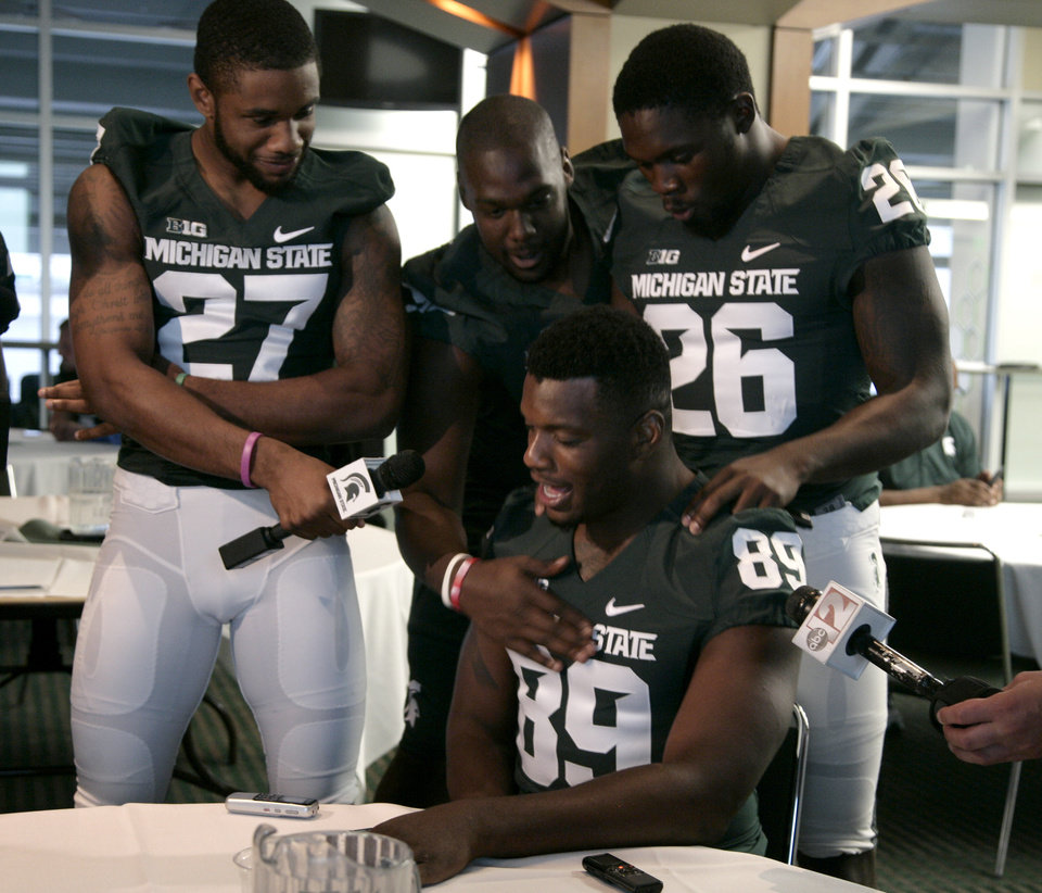 Photo - Michigan State's Shilique Calhoun (89) is interviewed by teammate Kurtis Drummond (27) as Joel Heath, center, and R.J. Williamson (26) tease him during the team's NCAA college football media day, Monday, Aug. 4, 2014, in East Lansing, Mich. (AP Photo/Al Goldis)