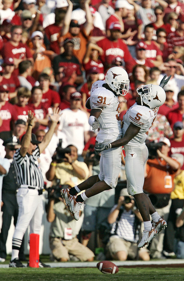 Photo - Texas' Aaron Ross (31) and Tarell Brown (5) celebrate after Ross scored a touchdown on fumble that was thrown behind the line of scrimmage in the second half during the University of Oklahoma Sooners (OU) college football game against the University of Texas (UT), in the Red River Shootout at the Cotton Bowl, on Saturday, Oct. 7, 2006, in Dallas, Tex.     by Chris Landsberger, The Oklahoman  ORG XMIT: KOD