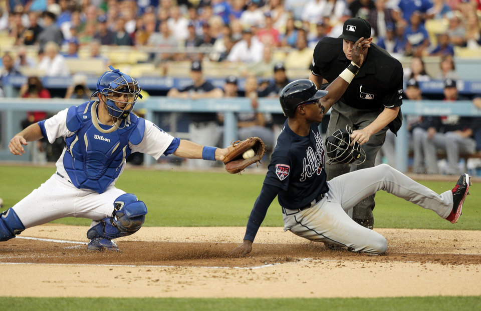 Photo - Atlanta Braves' B.J. Upton, right, scores on a sacrifice fly hit by Justin Upton as Los Angeles Dodgers catcher Drew Butera applies a late tag during the first inning of a baseball game on Tuesday, July 29, 2014, in Los Angeles. (AP Photo/Jae C. Hong)