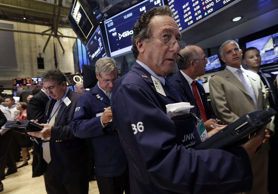 Photo - Trader Steven Kaplan, foreground right, works on the floor of the New York Stock Exchange Friday, July 18, 2014. U.S. stocks are opening higher after Google, Honeywell and other big companies report their quarterly results. (AP Photo/Richard Drew)