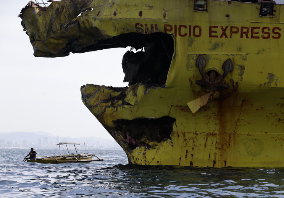 Photo - A volunteer paddles close to the damaged bow of the cargo ship Sulpicio Express Siete  Saturday Aug.17, 2013, a day after it collided with the passenger ferry MV Thomas of Aquinas off the coast of Talisay city, Cebu province, in central Philippines. Divers combed through a sunken ferry Saturday to retrieve the bodies of more than 200 people still missing from an overnight collision with a cargo vessel near the central Philippine port of Cebu that sent passengers jumping into the ocean and leaving many others trapped. At least 28 were confirmed dead and hundreds rescued. (AP Photo/Bullit Marquez)