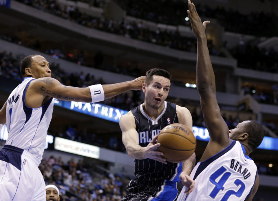 Dallas Mavericks\' Shawn Marion, left, and Elton Brand (42) defend as Orlando Magic\'s J.J. Redick makes a pass beneath the basket during the first half of an NBA basketball game Wednesday, Feb. 20, 2013, in Dallas. (AP Photo/Tony Gutierrez)