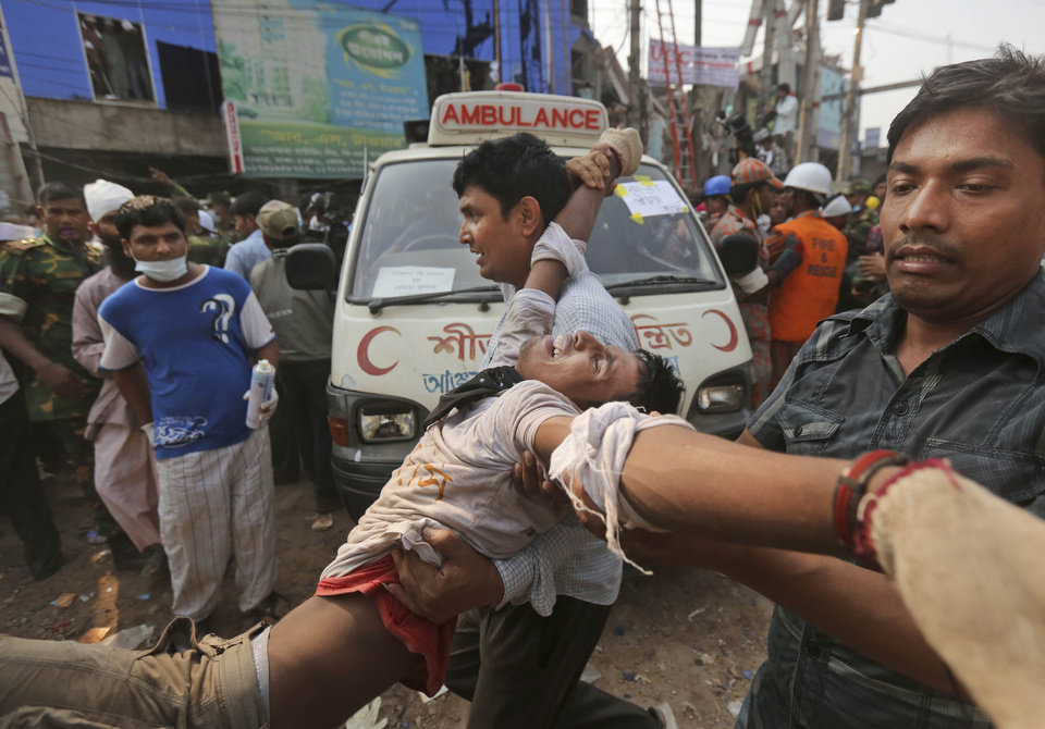 Photo - A Bangladeshi rescue worker, who was injured during a stampede caused by crowd panic over the rumor a section of the building might collapse, is carried at the site of a building that collapsed Wednesday in Savar, near Dhaka, Bangladesh, Friday, April 26, 2013. The death toll reached hundreds of people as rescuers continued to search for injured and missing, after a huge section of an eight-story building that housed several garment factories splintered into a pile of concrete. (AP Photo/Kevin Frayer)