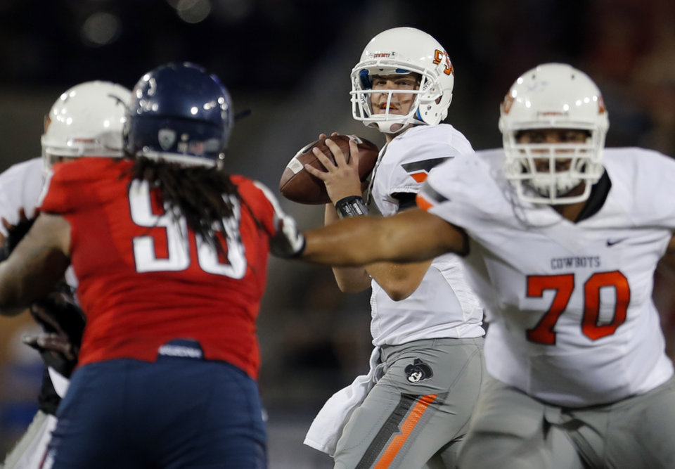 Photo - Oklahoma State's Wes Lunt (11) looks to throw a pass during the college football game between the University  of Arizona and Oklahoma State University at Arizona Stadium in Tucson, Ariz.,  Sunday, Sept. 9, 2012. Photo by Sarah Phipps, The Oklahoman
