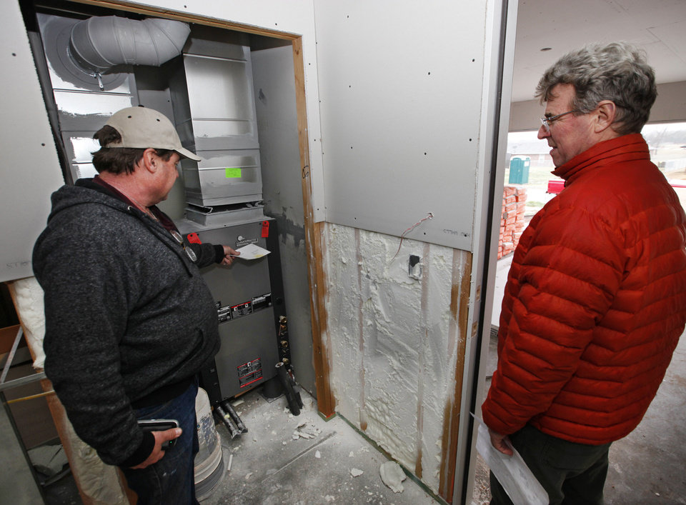 "Aaron McRee, construction manager for Central Oklahoma Habitat for Humanity, and TV personality Steve Thomas, national spokesman for Habitat for Humanity International, look over the heat pump in ""green"" and sustainable houses under construction. Photo by David McDaniel,  The Oklahoman"
