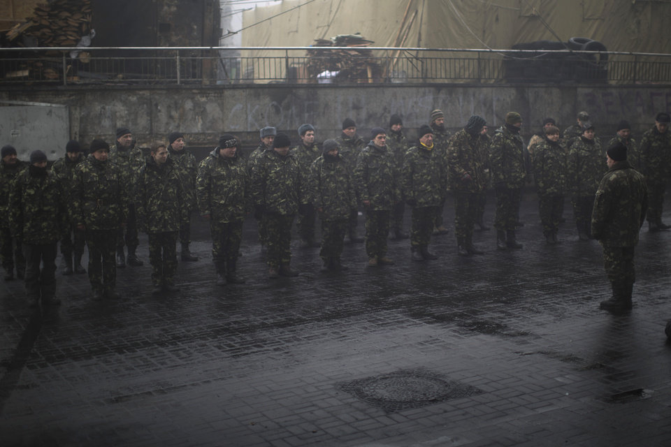 Photo - Ukrainian recruits line up as they receive military instructions from a commander at a recruitment center in Kiev's Independence Square, Ukraine, Tuesday, March 4, 2014. Vladimir Putin ordered tens of thousands of Russian troops participating in military exercises near Ukraine's border to return to their bases as U.S. Secretary of State John Kerry was on his way to Kiev. Tensions remained high in the strategic Ukrainian peninsula of Crimea with troops loyal to Moscow fired warning shots to ward off protesting Ukrainian soldiers. (AP Photo/Emilio Morenatti)