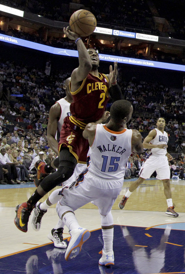 Photo - Cleveland Cavaliers' Kyrie Irving (2) drives into Charlotte Bobcats' Kemba Walker (15) during the first half of an NBA basketball game in Charlotte, N.C., Wednesday, April 17, 2013. Irving was called for a foul on the play. (AP Photo/Chuck Burton)