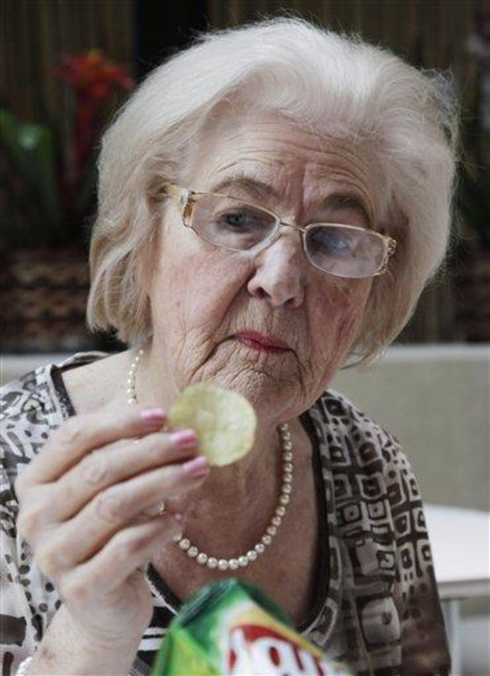 In this March 14, 2012 file photo, Marilyn Hagerty samples a Lays potato chip during an interview with The Associated Press in New York. While restaurateurs bemoaned the influence of Yelp and other social media review sites, Hagerty, the 85-year-old Grand Forks Herald restaurant columnist, cut through the noise, heaping near rhapsodic praise on the fine dining at her community's latest chain restaurant. All she wanted to do was get to her bridge game, but her review became a must-read sensation. (AP Photo/Mark Lennihan, File)