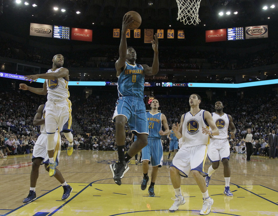 New Orleans Hornets small forward Al-Farouq Aminu (0) shoots in between Golden State Warriors point guard Jarrett Jack (2) and shooting guard Klay Thompson (11) during the second half of an NBA basketball game in Oakland, Calif., Wednesday, April 3, 2013. The Warriors won 98-88. (AP Photo/Jeff Chiu)