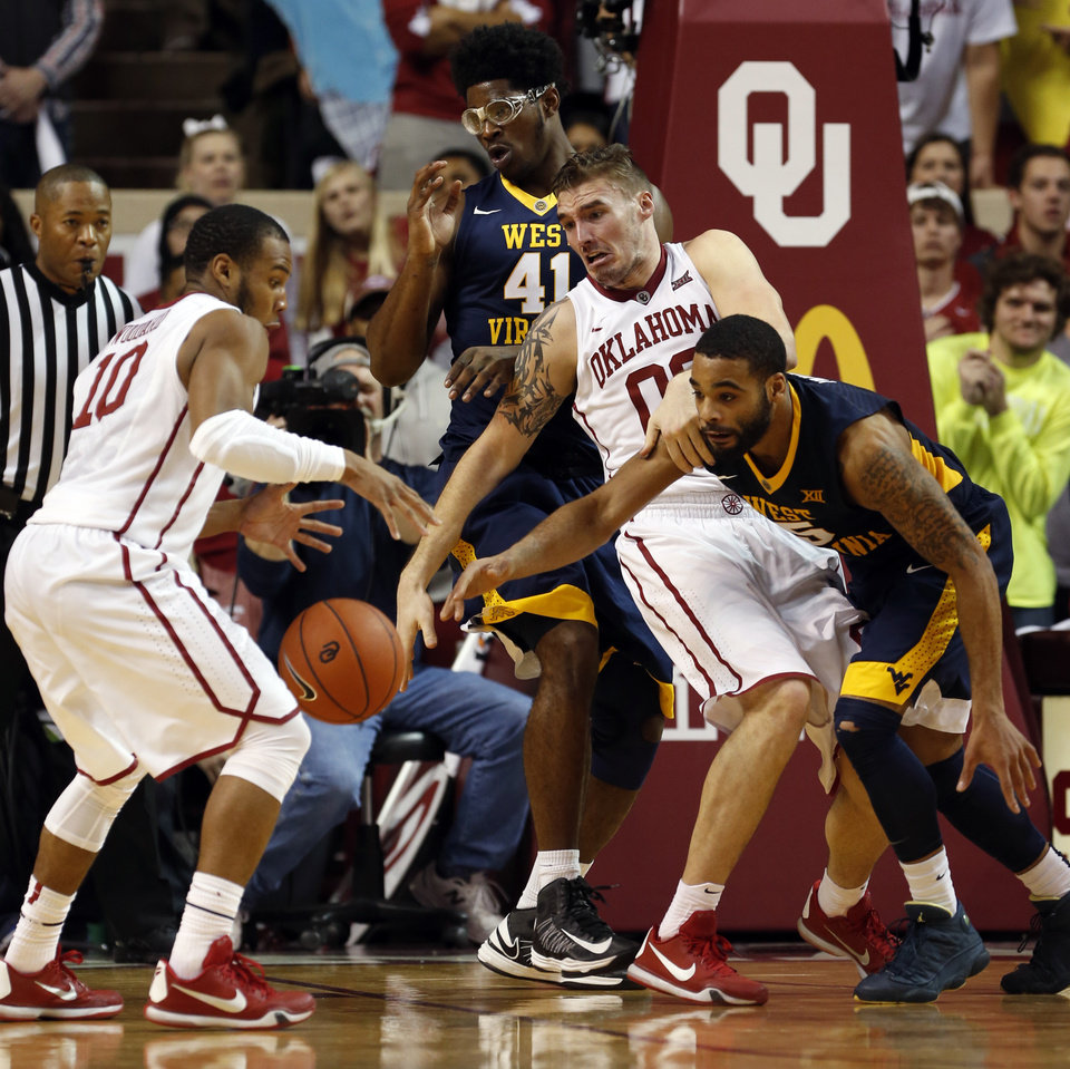 Photo - Oklahoma's Jordan Woodard (10) and Ryan Spangler (00) fight West Virginia's Jaysean Paige (5) for a rebound in the closing minute as the University of Oklahoma Sooner (OU) men defeat the West Virginia Mountaineers (WV) 70-68 in NCAA, college basketball at The Lloyd Noble Center on Jan. 16, 2016 in Norman, Okla. Photo by Steve Sisney, The Oklahoman