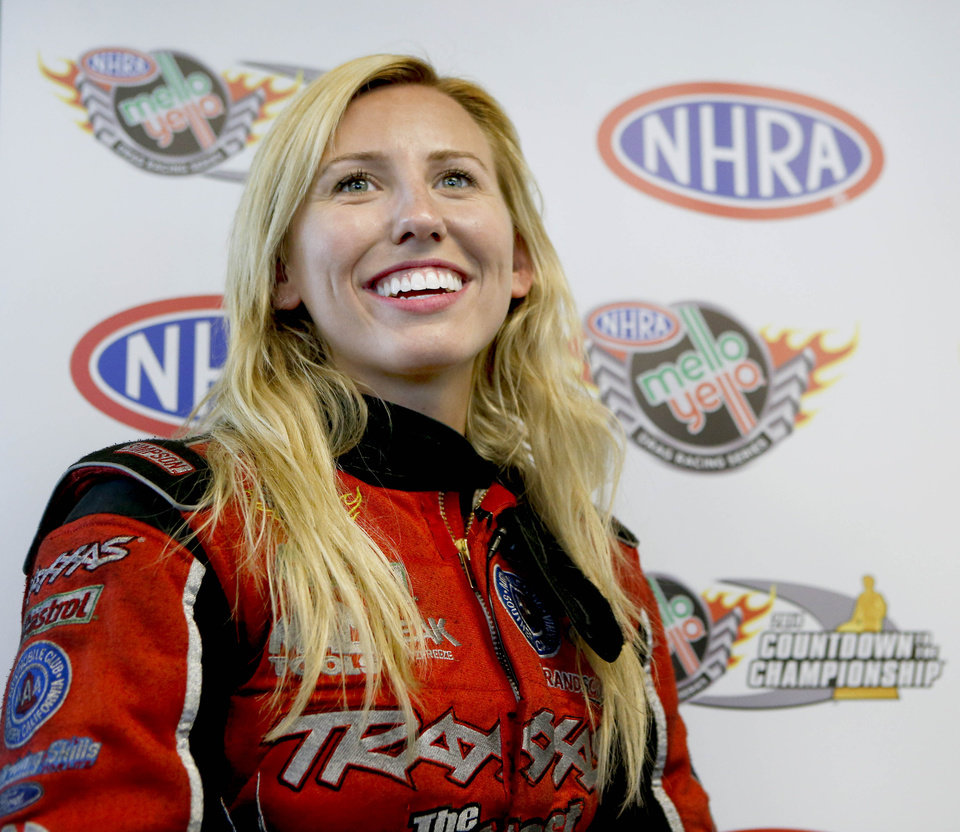Funny Car driver Courtney Force cracks a smile while talking about her qualifying run for the NHRA Kansas Nationals on Saturday May 24, 2014, that broke a track record at Heartland Park in Topeka, Kan., with a time of 4.009 seconds at 322.96 mph. (AP Photo/Topeka Capital-Journal, Chris Neal)