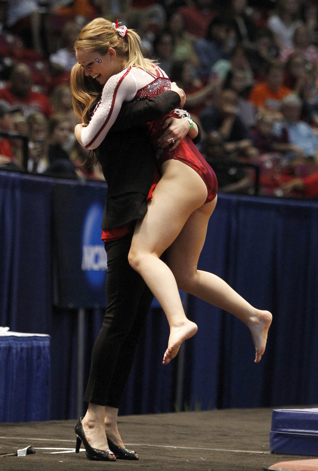Photo - Oklahoma's Haley Scaman, right, celebrates with coach KJ Kindler after her vault routine during the NCAA college women's gymnastics championships on Saturday, April 19, 2014, in Birmingham, Ala. (AP Photo/Butch Dill)