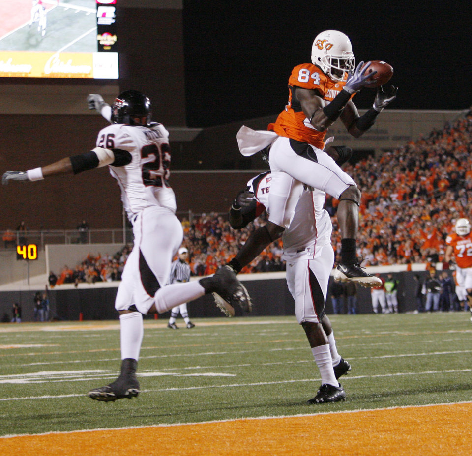 Photo - Cowboy Hubert Anyiam (84) catches a touchdown pass against Franklin Mitchem (26) and Jamar Wall (3) during the college football game between Oklahoma State University (OSU) and Texas Tech University at Boone Pickens Stadium in Stillwater, Okla. Saturday, Nov. 14, 2009. Photo by Nate Billings, The Oklahoman