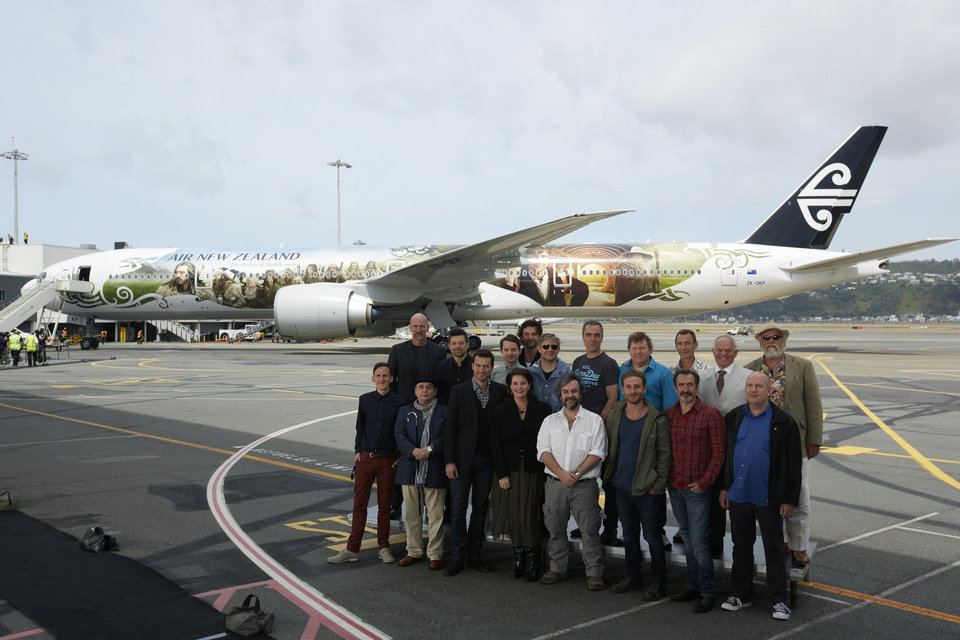 This photo released by Air New Zealand shows cast and crew including Peter Jackson, front center, posing for a photo in front of a 777-300 aircraft decorated with scenes and characters from the soon to be released,