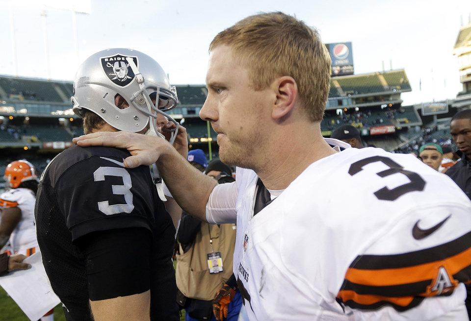 Photo - Cleveland Browns quarterback Brandon Weeden, right, greets Oakland Raiders quarterback Carson Palmer after an NFL football game in Oakland, Calif., Sunday, Dec. 2, 2012. The Browns won 20-17. (AP Photo/Marcio Jose Sanchez)