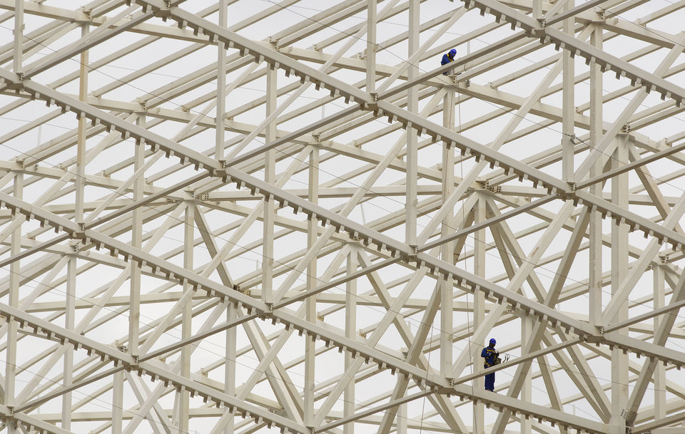 Photo - Men work amid the web rafters at Arena Corinthians in Sao Paulo, Brazil, Monday, Aug. 19, 2013. The new stadium will host the opening match of the World Cup in 2014. (AP Photo/Andre Penner)