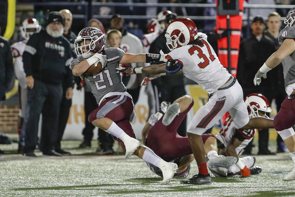 Photo - Jenks Will Cox (21) stiff arms OwassoÕs Andre King (37) on a run during the first quarter of the OSSAA 6A-1 Championship game in Edmond, Okla., Saturday, Dec. 7, 2019. (Alonzo Adams for The Oklahoman)