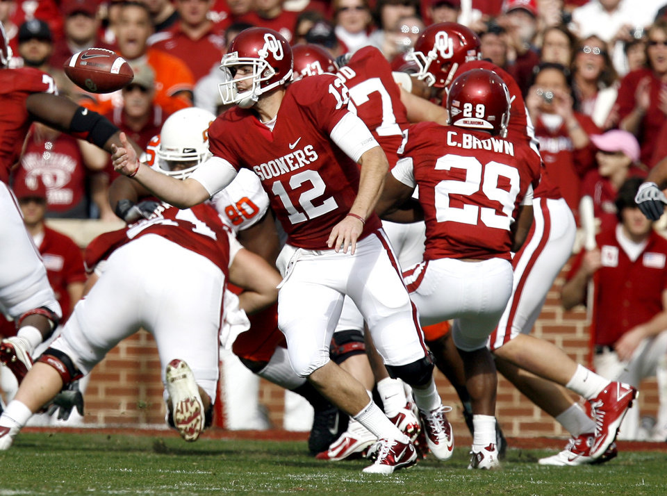 Photo - OU's Landry Jones (12) fumbles a snap during the first half of the Bedlam college football game between the University of Oklahoma Sooners (OU) and the Oklahoma State University Cowboys (OSU) at the Gaylord Family-Oklahoma Memorial Stadium on Saturday, Nov. 28, 2009, in Norman, Okla. Photo by Sarah Phipps, The Oklahoman