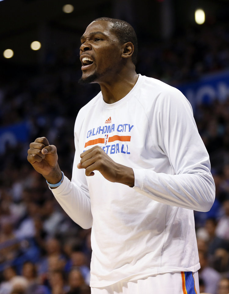 Photo - Oklahoma City's Kevin Durant (35) cheers on his teammates from the bench during an NBA basketball game between the Oklahoma City Thunder and the Denver Nuggets at the Chesapeake Energy Arena in Oklahoma City, Monday, March 24, 2014. Photo by Nate Billings, The Oklahoman