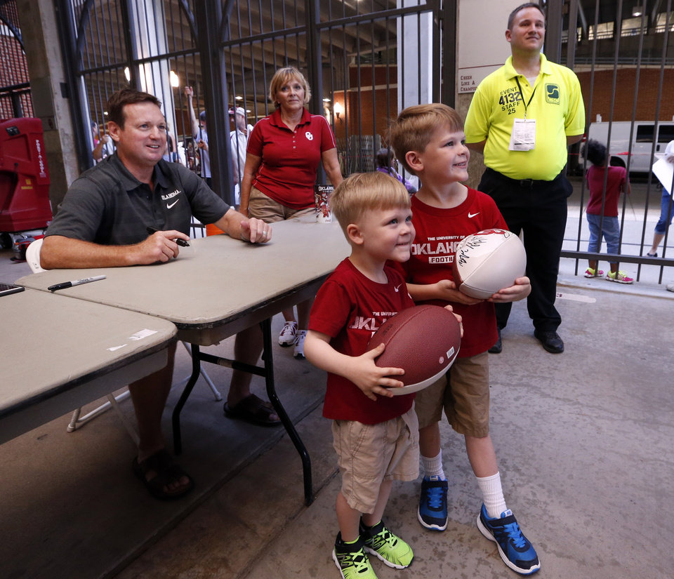 Photo - Bob Stoops poses with Walker, 4, and Davis Sanders, 6, of Kingfisher as he signs autographs during Meet the Sooners Day for the University of Oklahoma Sooners (OU) football team at Gaylord Family-Oklahoma Memorial Stadium in Norman, Okla., on Saturday, Aug. 8, 2015. Photo by Steve Sisney, The Oklahoman