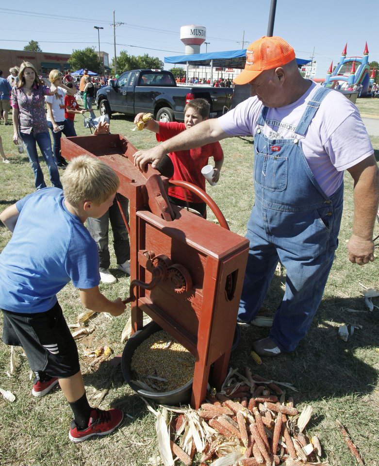 Fred Allen shows 11 year old Chandler Boothby how to process corn in a 90 year old machine, during the Mustang Western Days celebration in Mustang, OK, Saturday, September 8, 2012, By Paul Hellstern, The Oklahoman