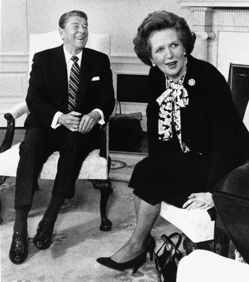 Photo - FILE - In this Feb. 20, 1985 file photo, British Prime Minister Margaret Thatcher turns to look at the crush of photographers in the Oval Office as President Reagan laughs during a photo session at the White House in Washington. It's been most of three decades since debate over