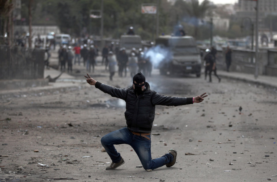 A masked Egyptian protester part of the Black Bloc, flashes the victory sign during clashes with riot police, background, near Tahrir Square, Cairo, Egypt, Monday, Jan. 28, 2013.  An unpredictable new element has entered Egypt's wave of political unrest, a mysterious group of black-masked young men calling themselves the Black Bloc. They present themselves as the defenders of protesters against the rule of President Mohammed Morsi, but Islamists have used them to depict the opposition as a violent force wrecking the nation. (AP Photo/Khalil Hamra)