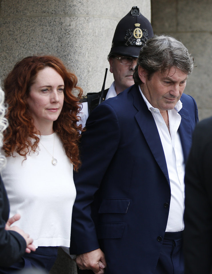 Photo - Rebekah Brooks, former News International chief executive, left, accompanied by her husband Charlie Brooks, leaves the Central Criminal Court in London, Tuesday, June 24, 2014. Former News of the World editor Andy Coulson was convicted of phone hacking Tuesday, but fellow editor Rebekah Brooks was acquitted after a monthslong trial centering on illegal activity at the heart of Rupert Murdoch's newspaper empire. A jury at London's Old Bailey unanimously found Coulson, the former spin doctor of British Prime Minister David Cameron, guilty of conspiring to intercept communications. Brooks was acquitted of that charge and of counts of bribing officials and obstructing police. The nearly eight-month trial was triggered by revelations that for years the News of the World used illegal eavesdropping to get stories, listening in on the voicemails of celebrities, politicians and even crime victims. (AP Photo/Lefteris Pitarakis)