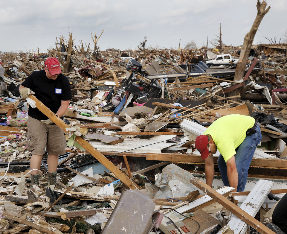 Photo - Michael reed, left, and Brett Droy pull loose boards from the rubble of a home. They are volunteers from the First Baptist Church of Moore. Volunteers from various parts of the country joined Oklahomans in assisting residents on Saturday,  May 25, 2013, doing whatever was needed to remove debris and salvage items from this neighborhood east of Santa Fe, north of SW 19 Street.  An EF5 tornado leveled many neighborhoods in Moore and southwest Oklahoma City last Monday.   Photo  by Jim Beckel, The Oklahoman.