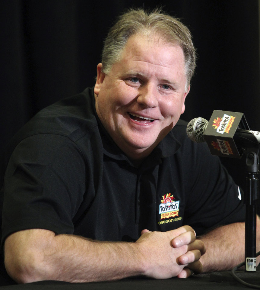 FILE - In this Jan. 3, 2013 file photo, Oregon head coach Chip Kelly laughs as he answers a reporter\'s question during media day for the Fiesta Bowl NCAA college football game in Scottsdale, Ariz. The Philadelphia Eagles have hired Kelly after he originally chose to stay at Oregon. Kelly becomes the 21st coach in team history and replaces Andy Reid, who was fired on Dec. 31 after a 4-12 season. (AP Photo/Paul Connors, File)