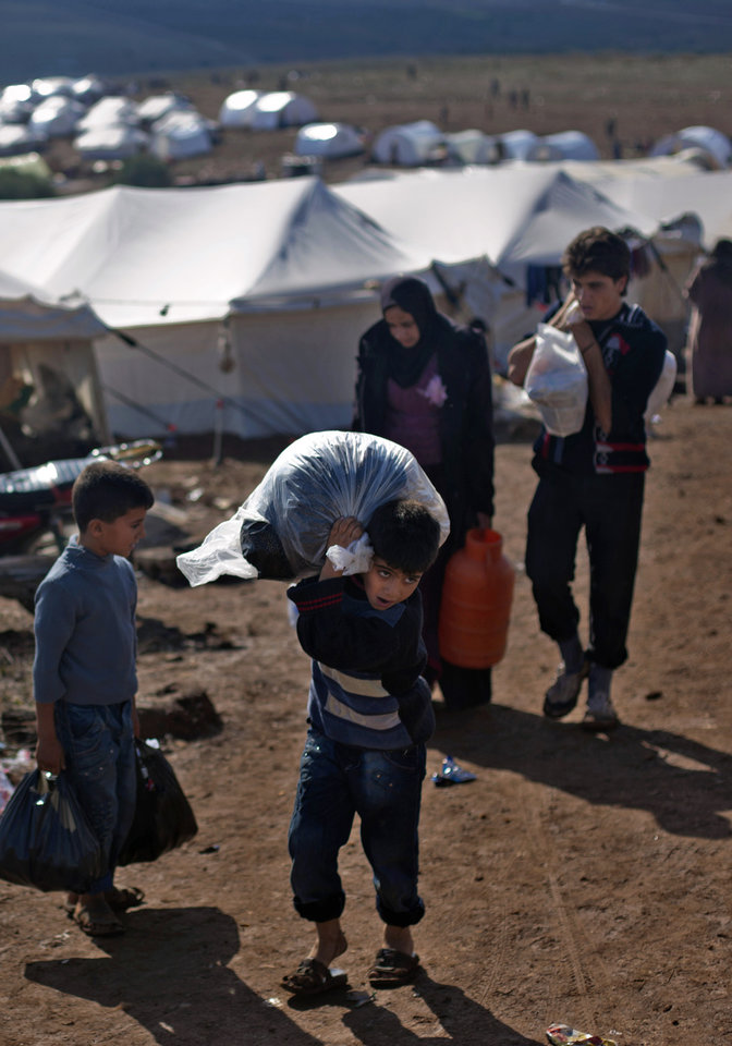 Photo -   A Syrian boy who fled with his family from the violence in their village, carries a plastic bag as he walks to his tent at a displaced camp, in the Syrian village of Atma, near the Turkish border with Syria. Saturday, Nov. 10, 2012. (AP Photo/ Khalil Hamra)