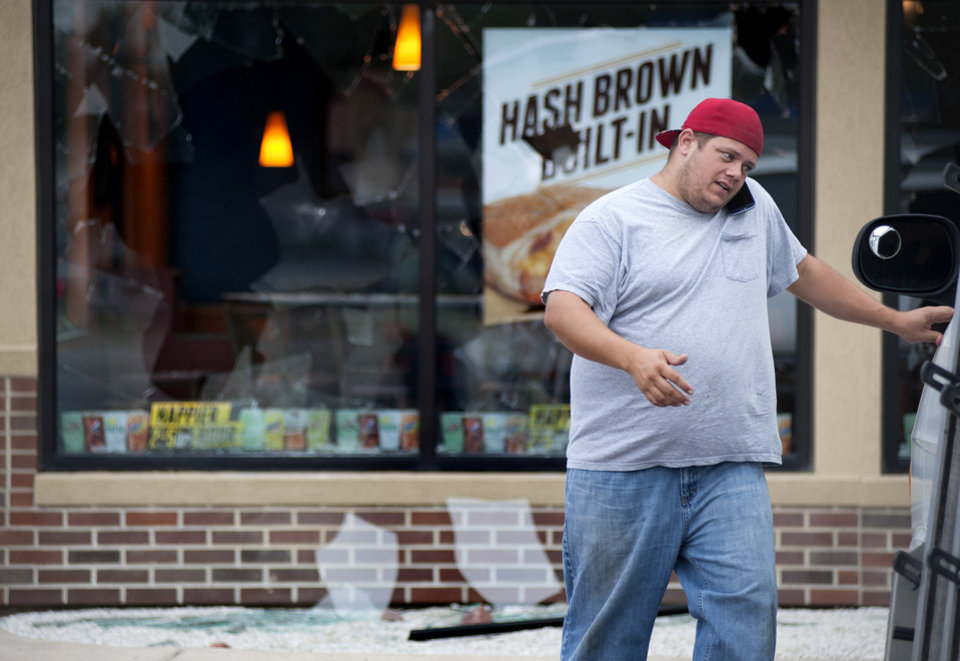 Photo - Kevin Nelke, of A-Affordable Glass, takes measurements and calls in an order Monday, Aug. 11, 2014, while repairing the windows of the Taco Bell looted during the violence that erupted overnight in Ferguson, Mo., following a candle-light memorial for 18-year-old shooting victim Michael Brown. Police said Brown, who was unarmed, was fatally shot Saturday in a scuffle with an officer.  (AP Photo/Sid Hastings)
