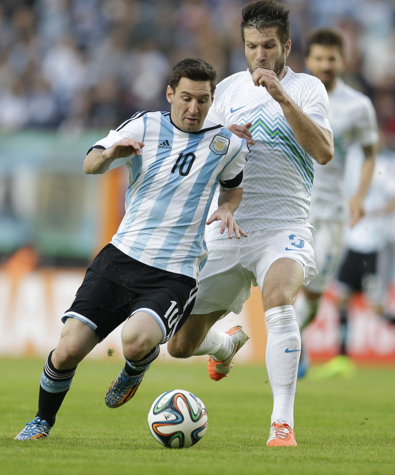 Photo - Argentina's Lionel Messi, left, fights for the ball with Slovenia's Bostjan Cesar during their international friendly soccer match in La Plata, Argentina, Saturday, June 7, 2014. Argentina's team is leaving June 9 for Brazil to compete in the World Cup. (AP Photo/Natacha Pisarenko)