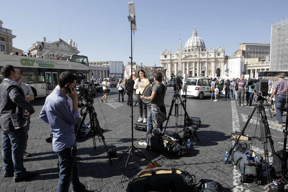 TV journalists stand up in front of the Vatican, Saturday, Oct. 6, 2012. The verdict in the case of the pope\'s butler accused of leaking papal documents is expected Saturday Oct. 6, 2012, and may help close one of the most damaging scandals of Pope Benedict XVI\'s papacy. (AP Photo/Riccardo De Luca)