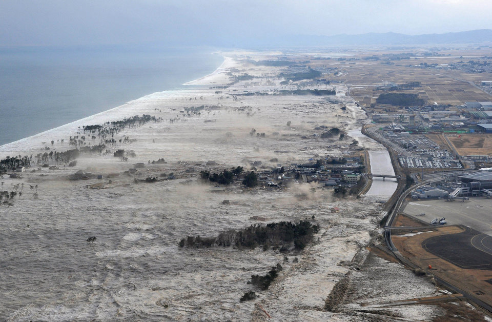 Photo - Earthquake-triggered tsumanis sweep shores along Iwanuma in northern Japan on Friday March 11, 2022. The magnitude 8.9 earthquake slammed Japan's eastern coast Friday, unleashing a 13-foot (4-meter) tsunami that swept boats, cars, buildings and tons of debris miles inland.  (AP Photo/Kyodo News) JAPAN OUT, MANDATORY CREDIT, FOR COMMERCIAL USE ONLY IN NORTH AMERICA ORG XMIT: TOK841