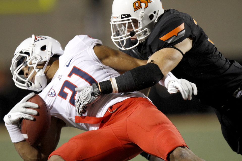 Photo - Oklahoma State's Alex Elkins (37) brings down Arizona's Gino Crump (21) during a college football game between the Oklahoma State University Cowboys (OSU) and the University of Arizona Wildcats at Boone Pickens Stadium in Stillwater, Okla., Thursday, Sept. 8, 2011. Photo by Bryan Terry, The Oklahoman  ORG XMIT: KOD
