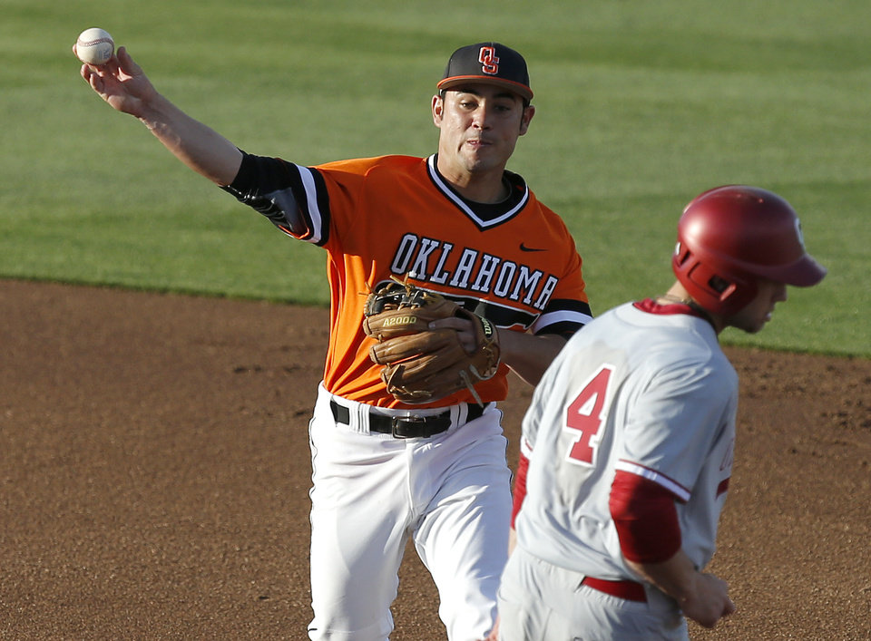 Photo - OSU's Tim Arakawa throws past OU's Hunter Haley for a double play in the first inning of a Bedlam baseball game between Oklahoma State University and the University of Oklahoma in Stillwater, Okla.,Tuesday, April 15, 2014. Photo by Bryan Terry, The Oklahoman